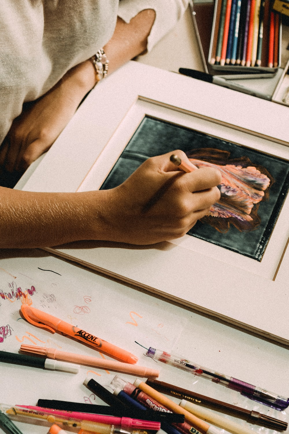 person holding white framed painting