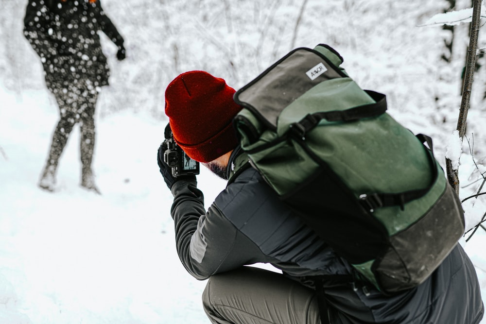 woman in black jacket and red knit cap holding black dslr camera