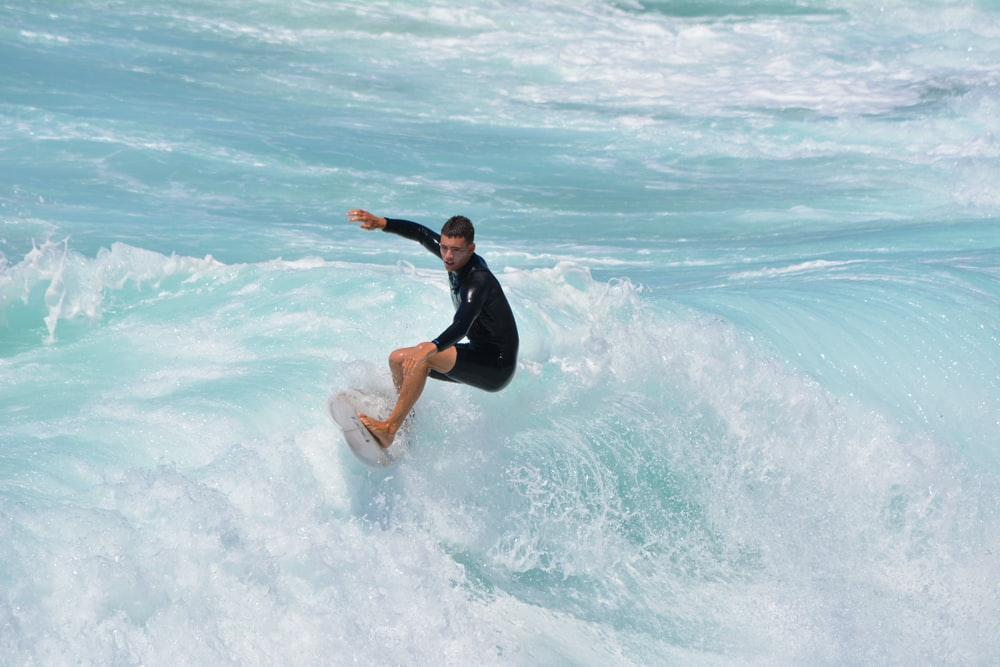 woman in black wetsuit surfing on sea waves during daytime