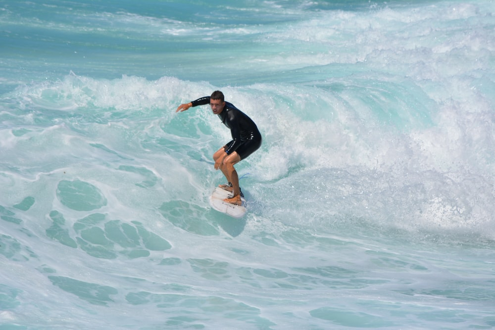 man in black shirt and shorts surfing on sea waves during daytime
