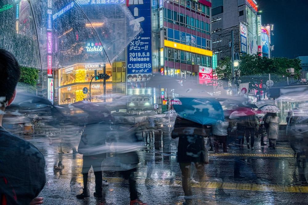 person in black jacket holding umbrella walking on sidewalk during rain
