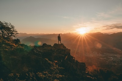 silhouette of person standing on rock during sunset