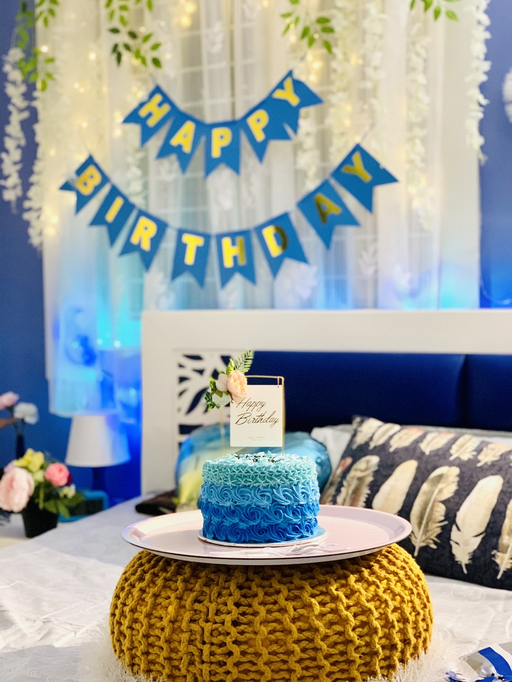 blue and white floral cake on brown wooden round table