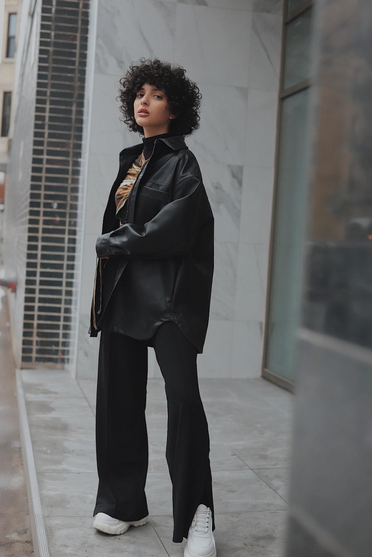 woman in black coat standing on white floor
