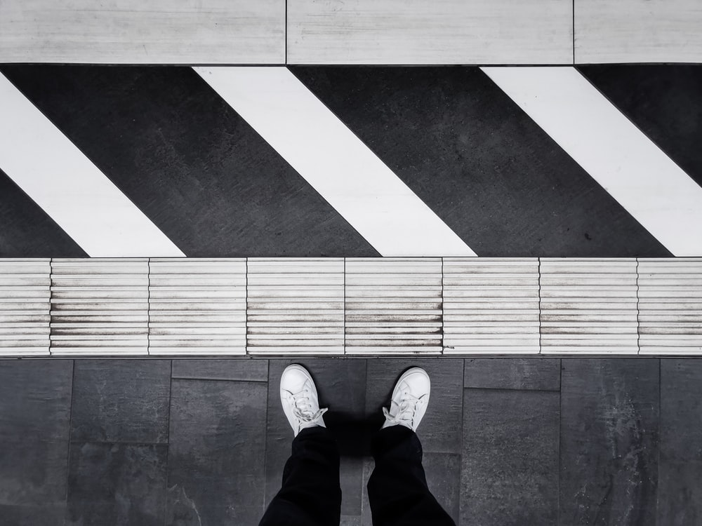 person in black pants and white sneakers standing on black and white floor