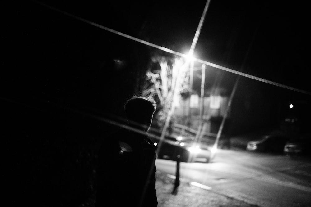 man in black jacket standing on sidewalk during night time