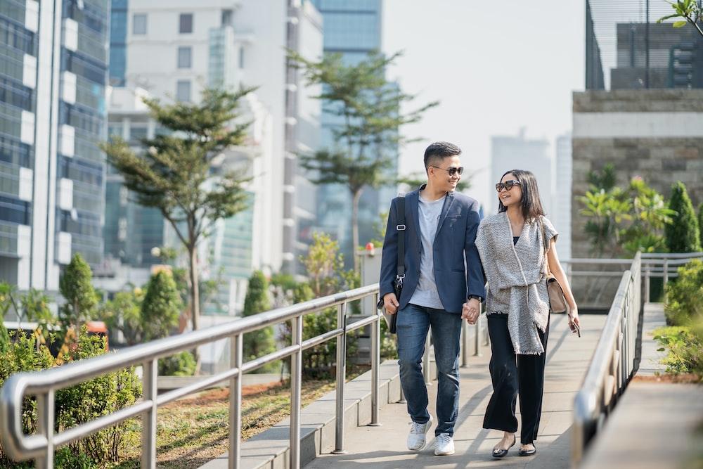 man in black suit jacket standing beside woman in gray coat