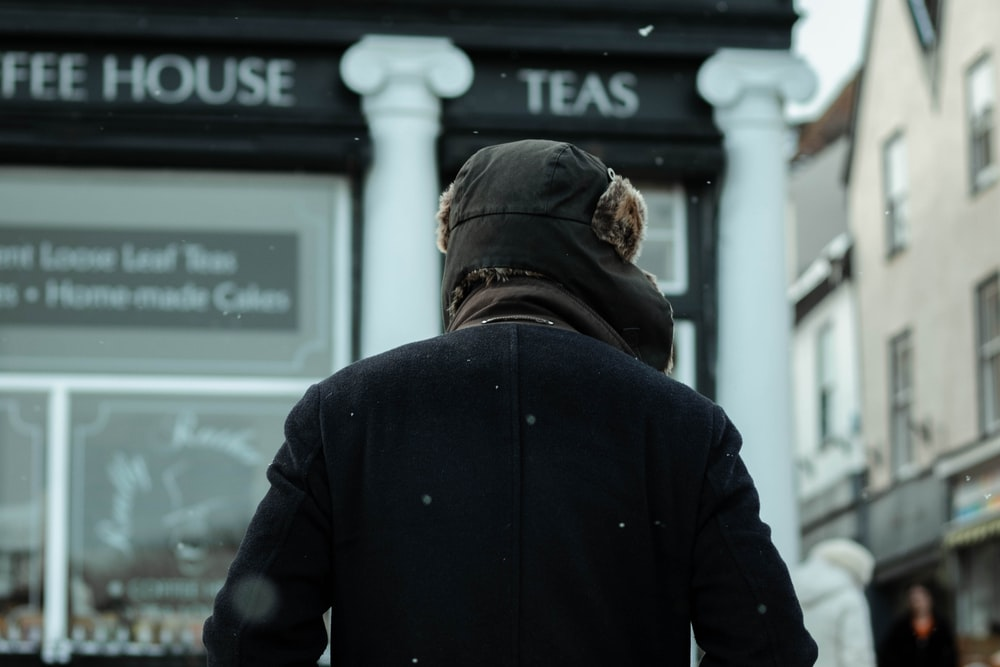 man in black jacket and brown knit cap