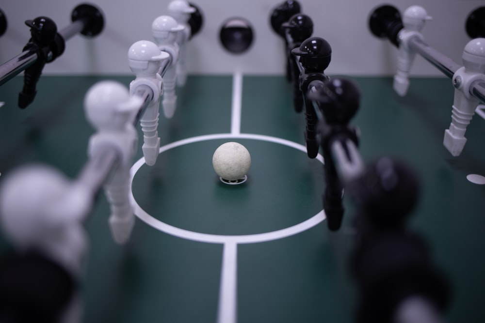 white and black soccer ball on green and white court