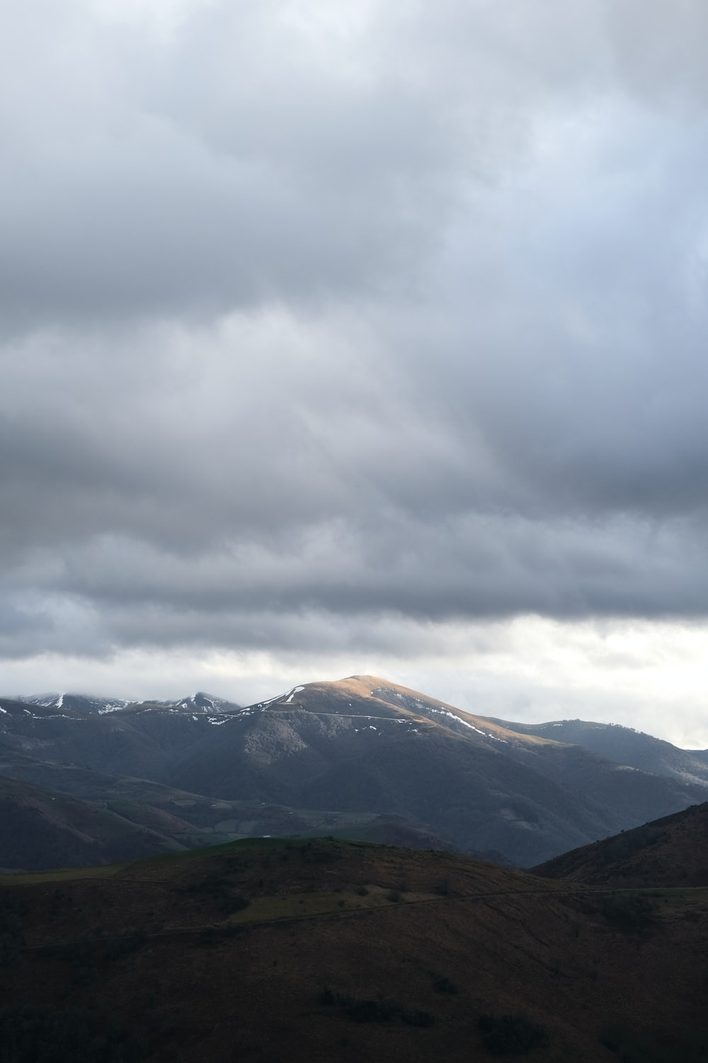 green and brown mountains under white clouds during daytime