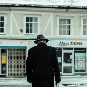 man in black coat walking on snow covered ground during daytime