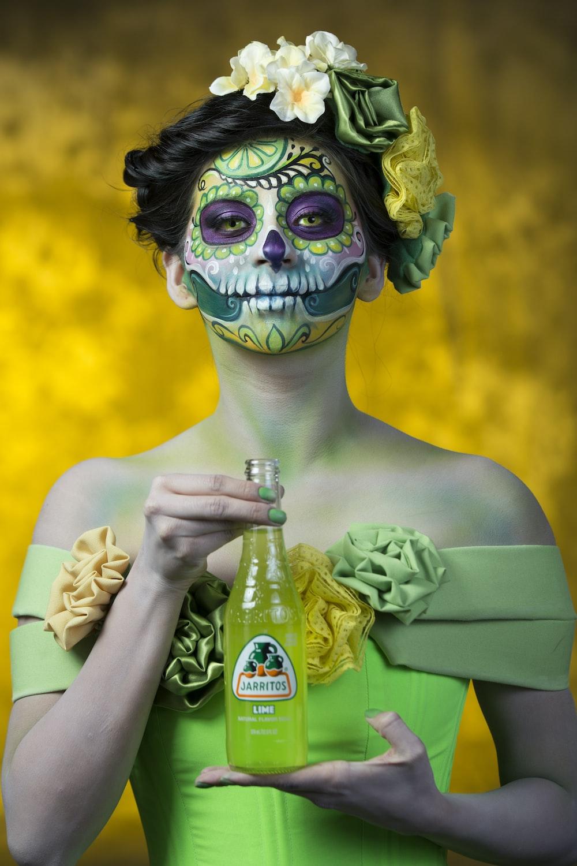 woman in green dress holding glass bottle