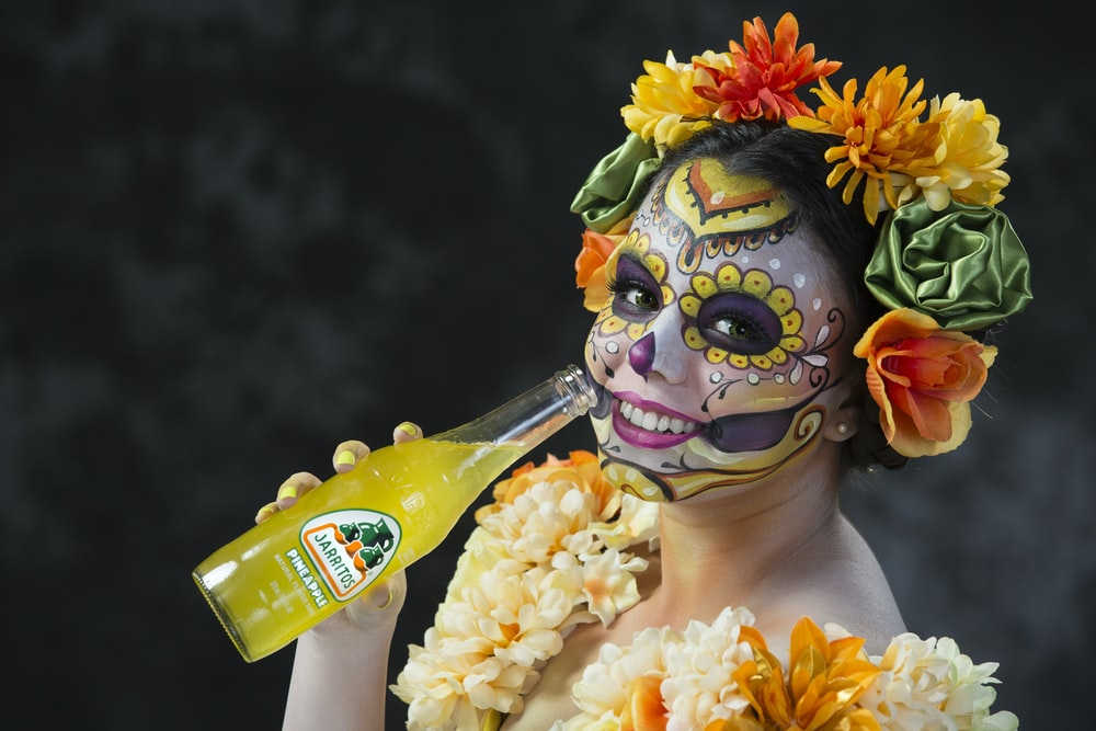 person in yellow green and red floral headdress holding yellow and white plastic bottle