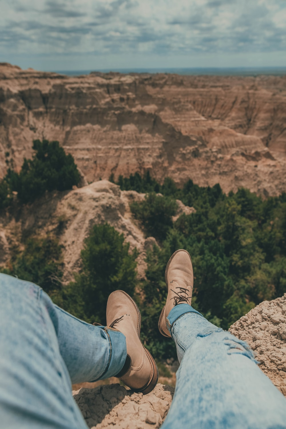 person in blue denim jeans and brown shoes sitting on rock formation during daytime