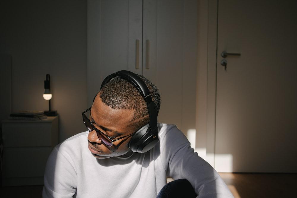 man in white long sleeve shirt wearing black headphones