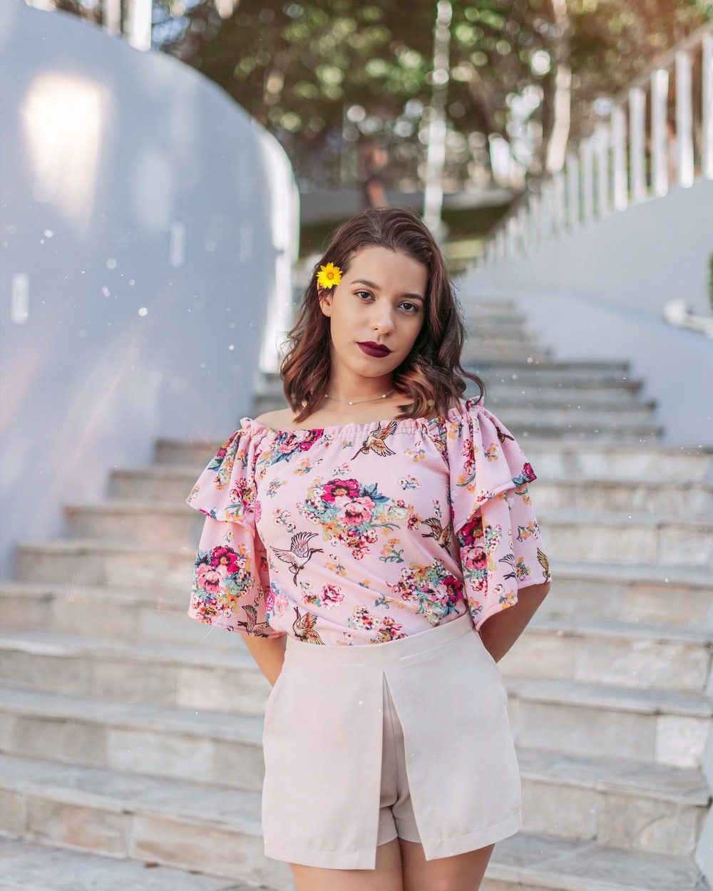 woman in pink and white floral shirt and white pants standing on concrete stairs