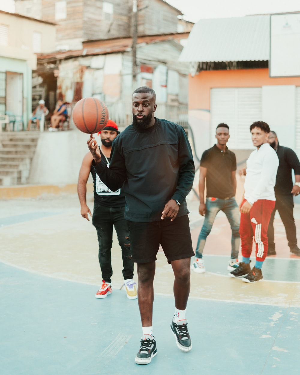 man in black polo shirt holding basketball