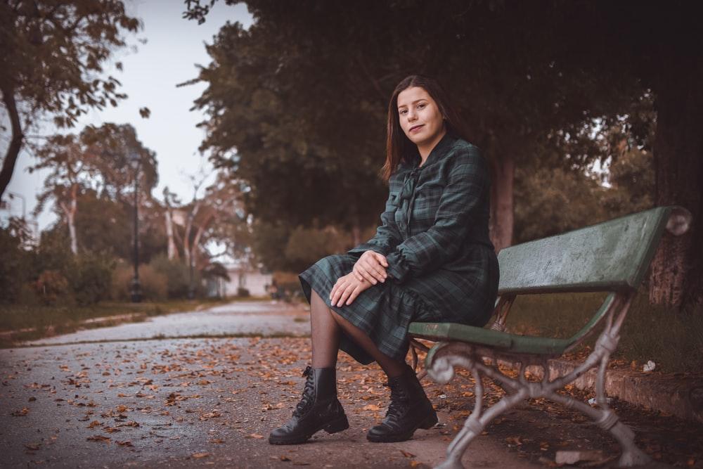 woman in black leather jacket sitting on brown wooden bench
