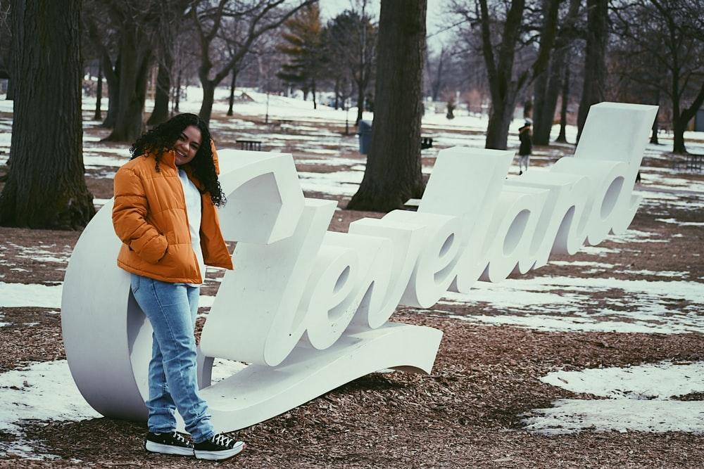 woman in orange jacket and blue denim jeans standing near white wooden bench during daytime