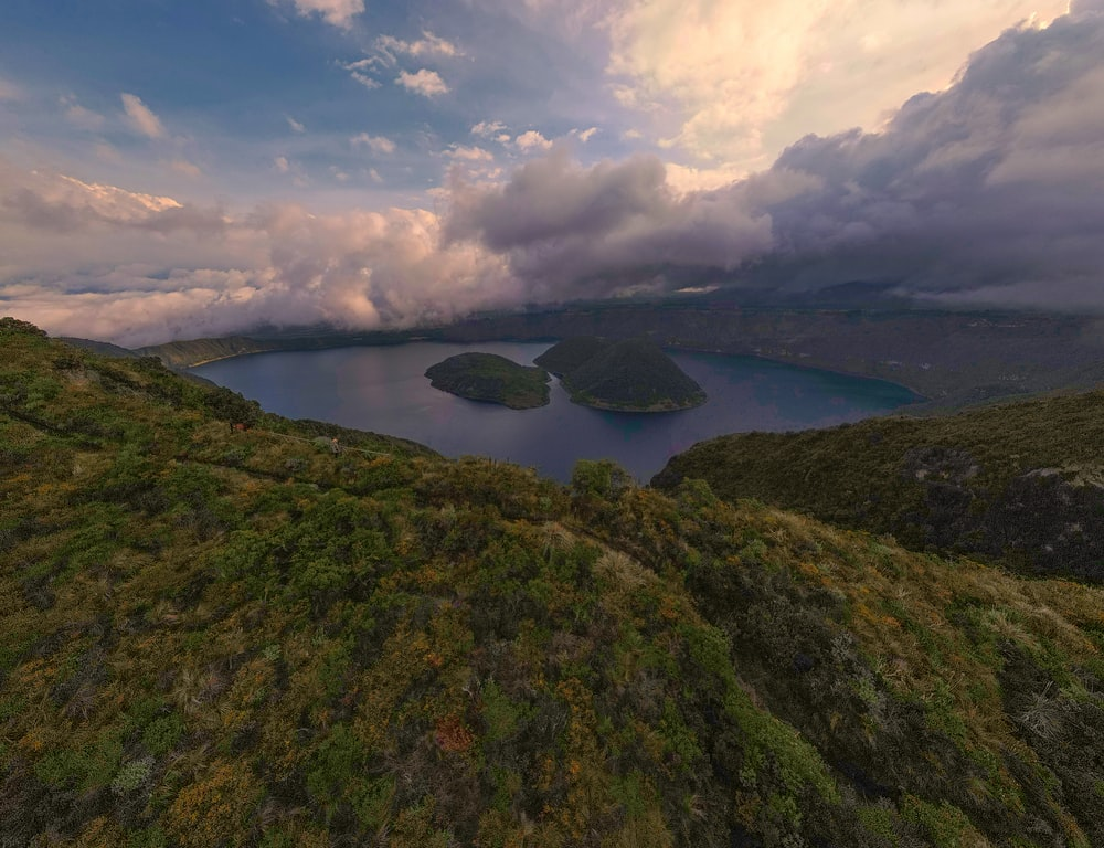 aerial view of lake between green mountains under cloudy sky during daytime