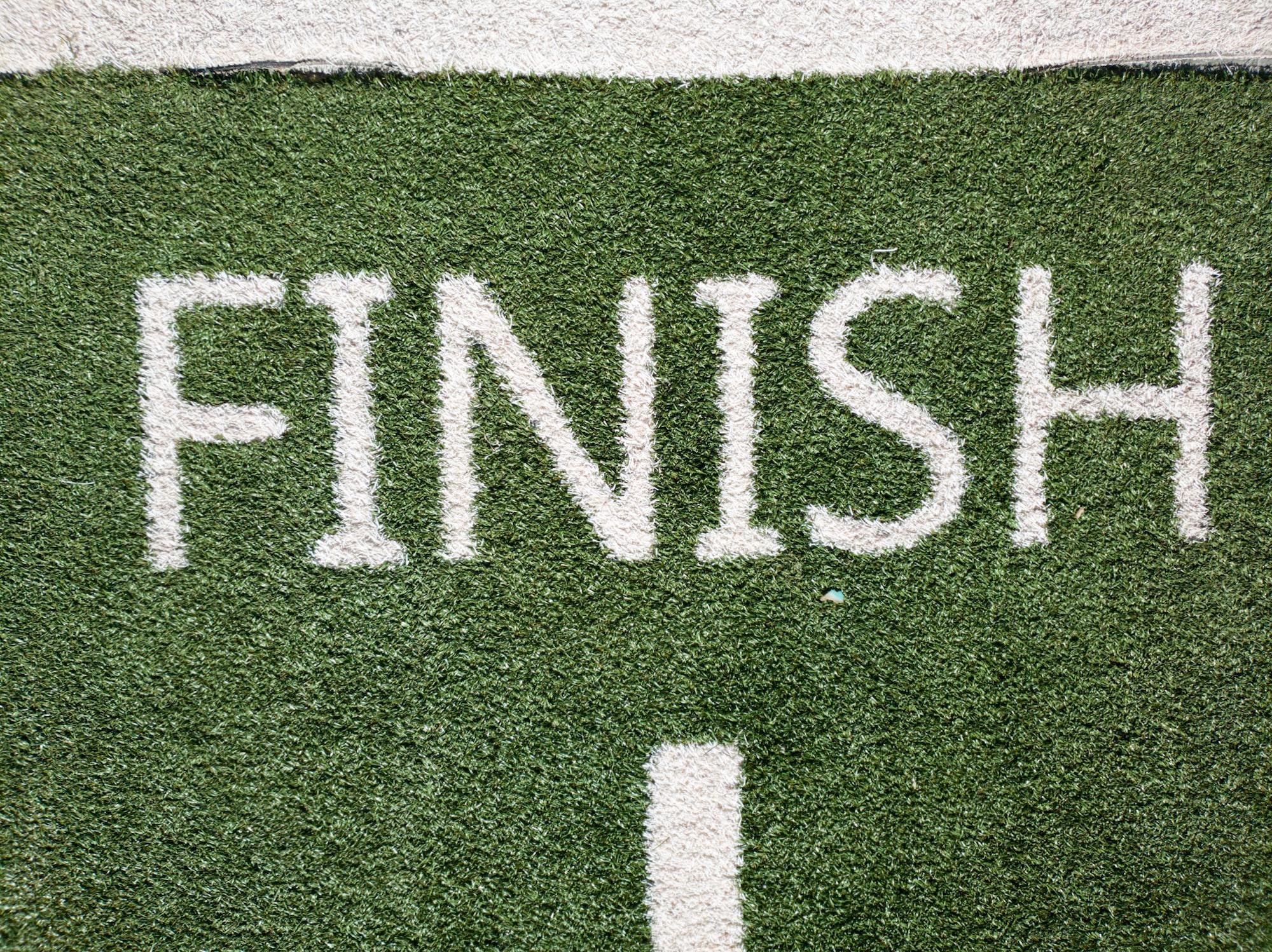 The word Finish in green turf