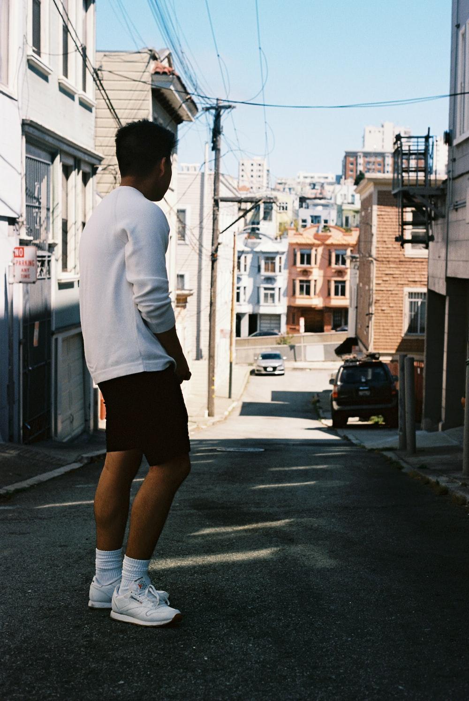 man in white dress shirt and black shorts standing on sidewalk during daytime