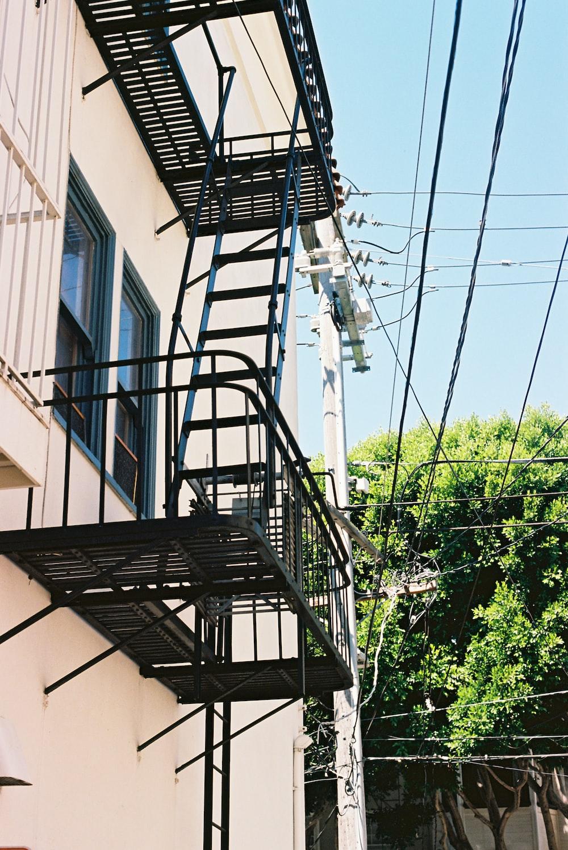 black metal staircase near white concrete building during daytime