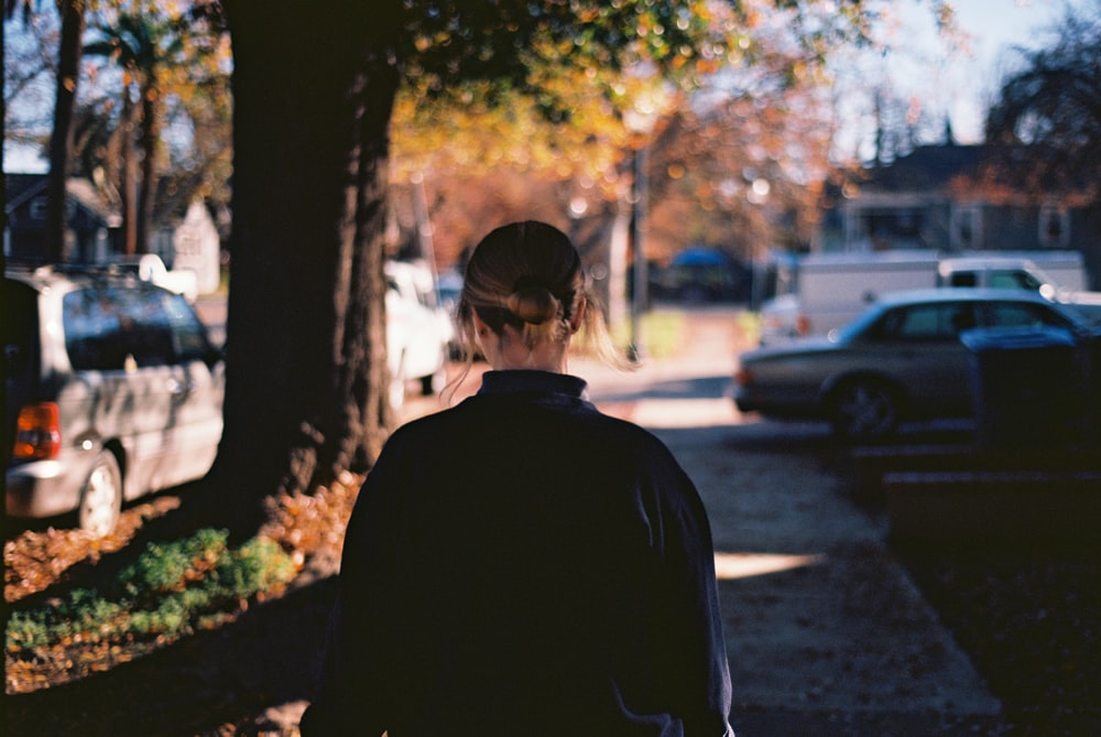 man in black jacket standing near trees during daytime
