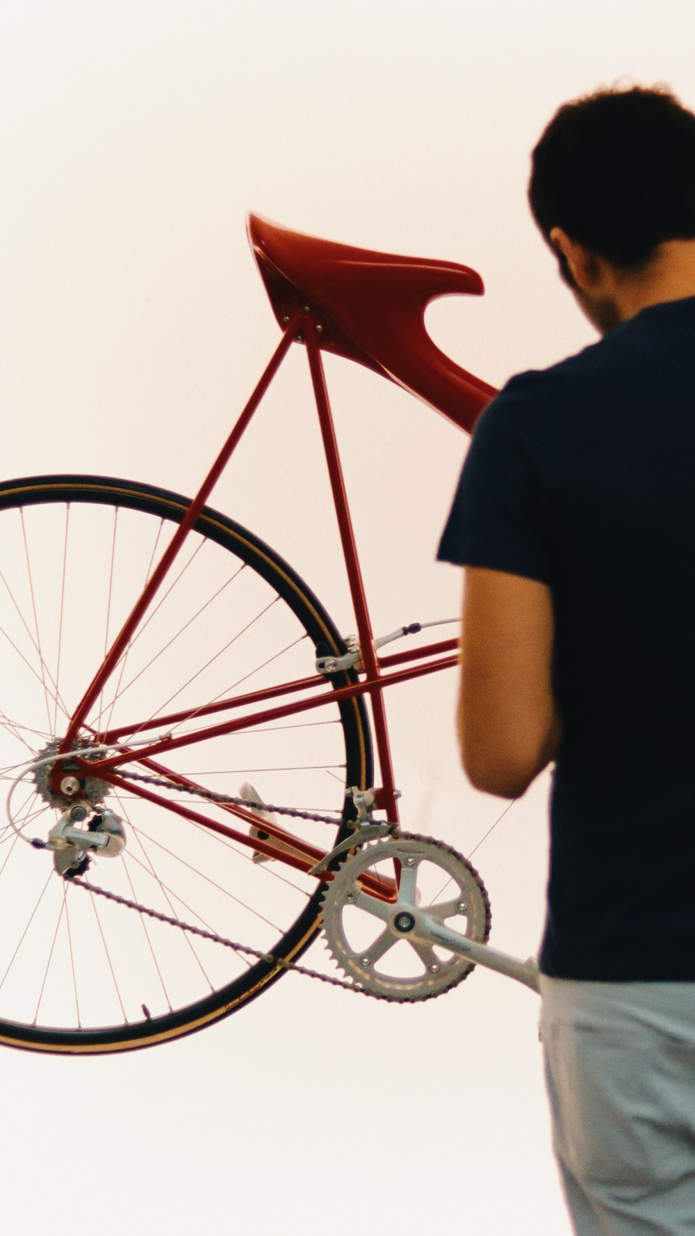 man in black t-shirt standing beside red bicycle