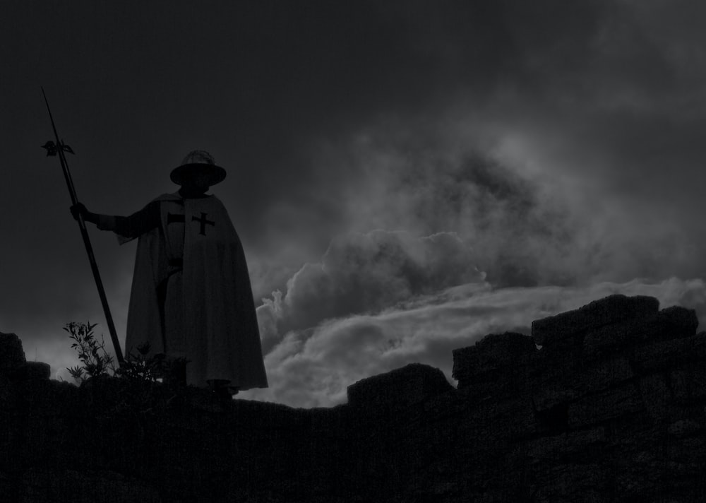 person in white robe standing on rock formation under gray clouds