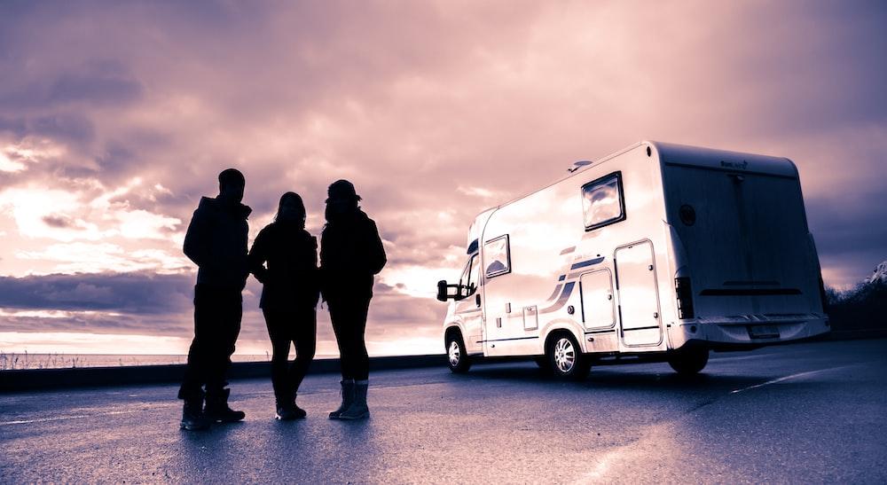 silhouette of 3 men standing near white van