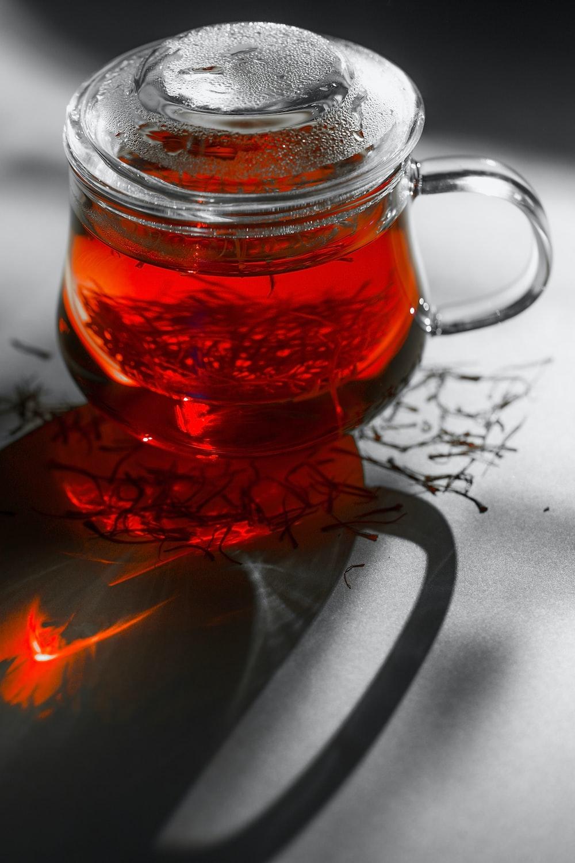 clear glass mug with red liquid inside