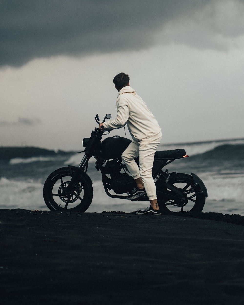 man in white robe riding black motorcycle
