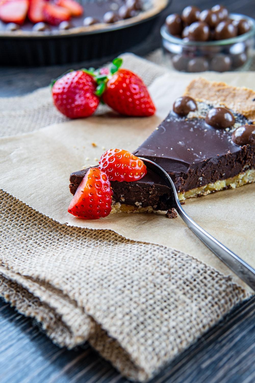 strawberry on brown cake on white textile