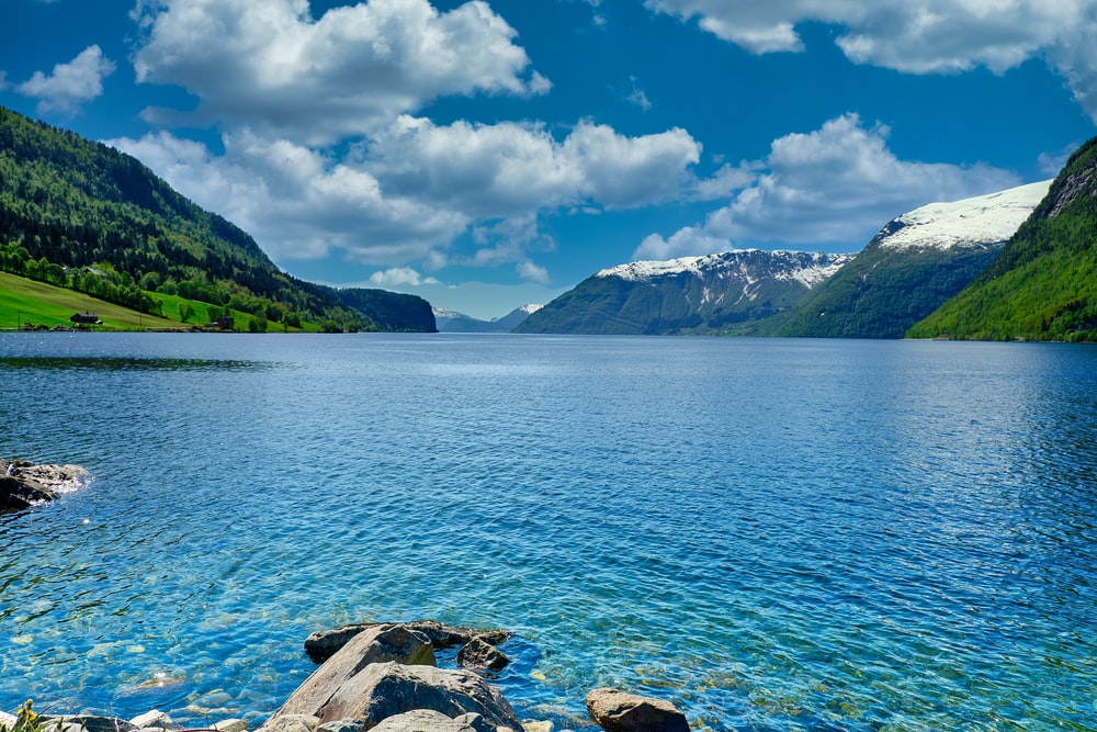 body of water near mountain under blue sky during daytime