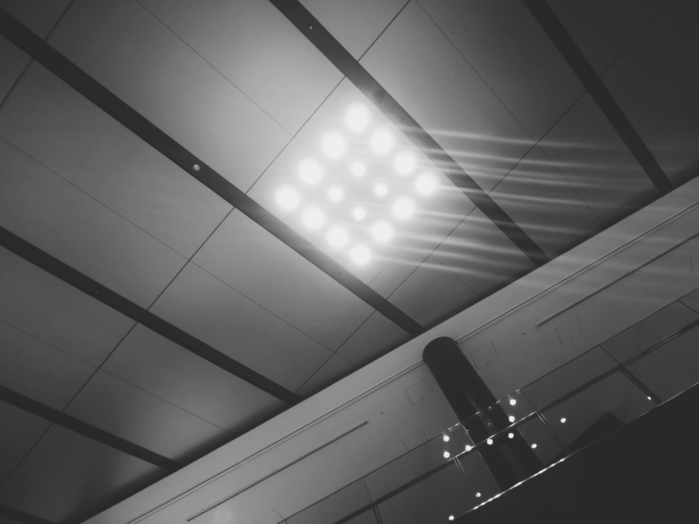 white ceiling with lights turned on in grayscale photography