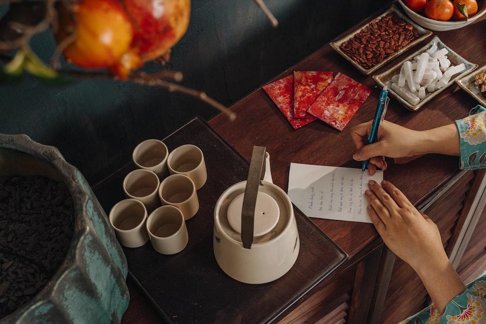 person writing on white paper beside white ceramic mug