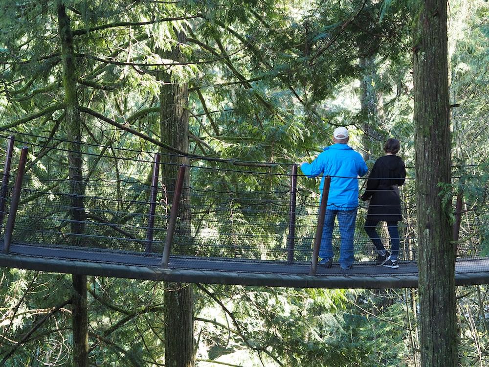 man in blue jacket and black pants standing on brown wooden bridge