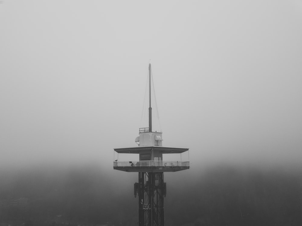 black and white tower in the middle of fog