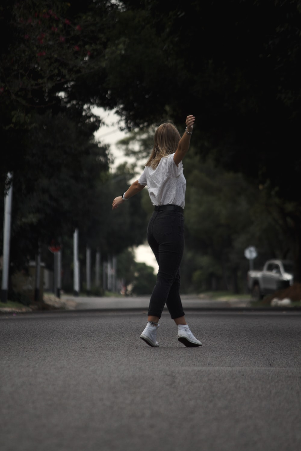 woman in white shirt and black pants running on road during daytime