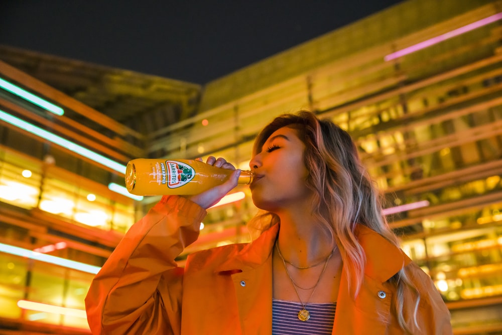 woman in orange blazer drinking from bottle