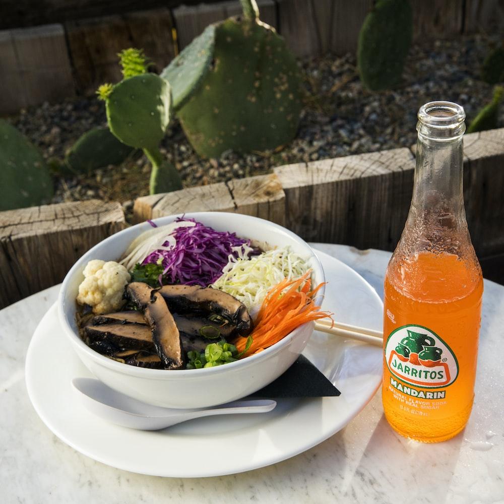 vegetable salad on white ceramic plate beside orange juice bottle