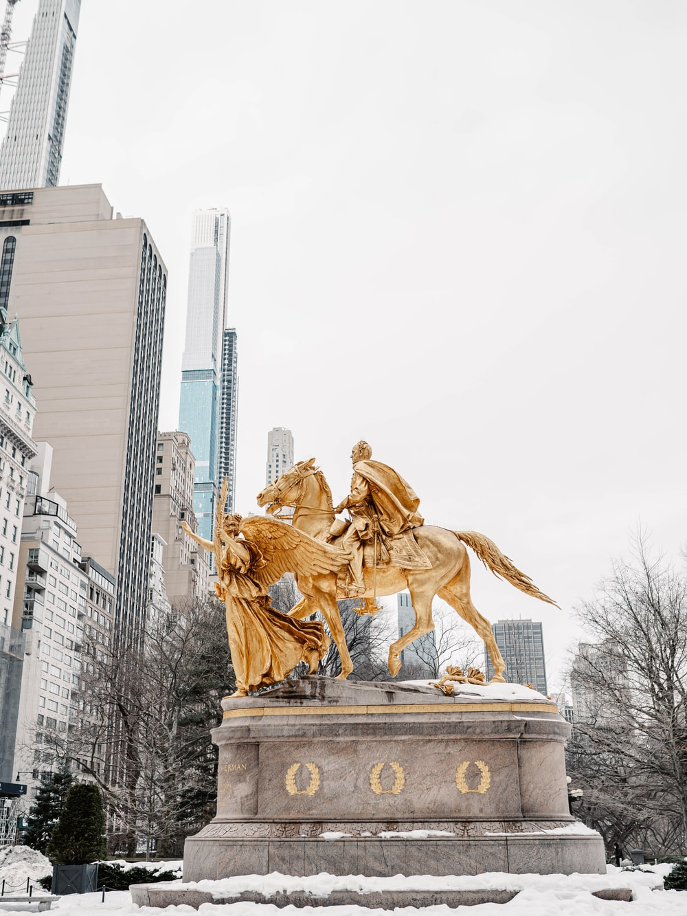 gold statue of man riding horse near high rise buildings during daytime
