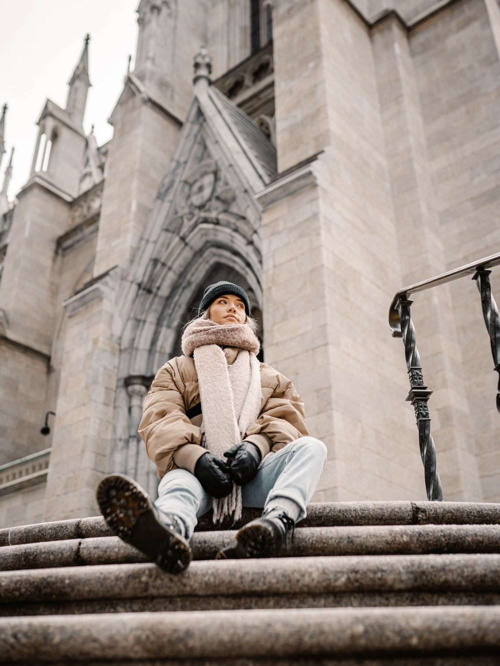 man in brown coat sitting on concrete bench