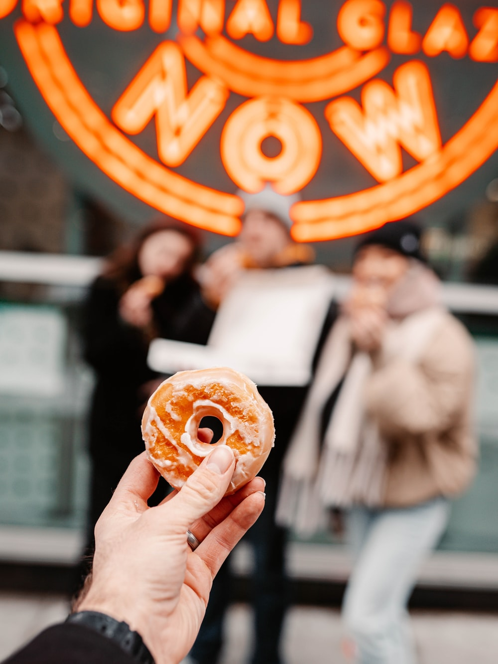 person holding brown donut with orange and white toppings