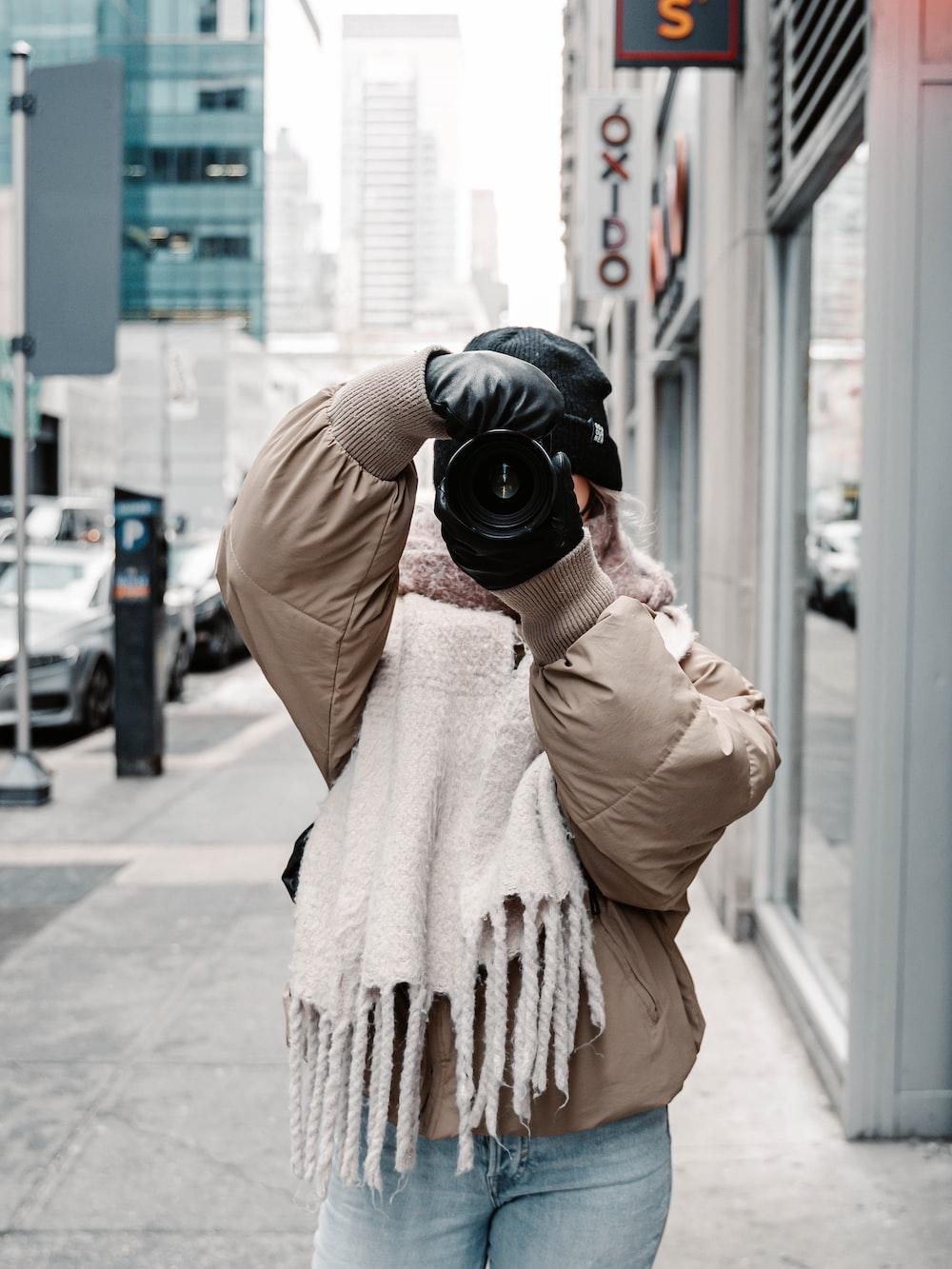 person in brown coat holding black dslr camera