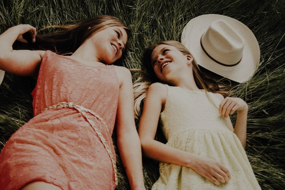 2 women lying on grass field