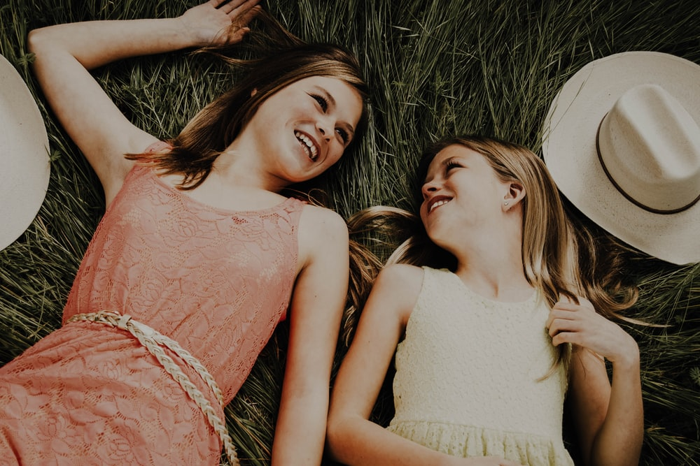 2 women lying on brown grass field during daytime