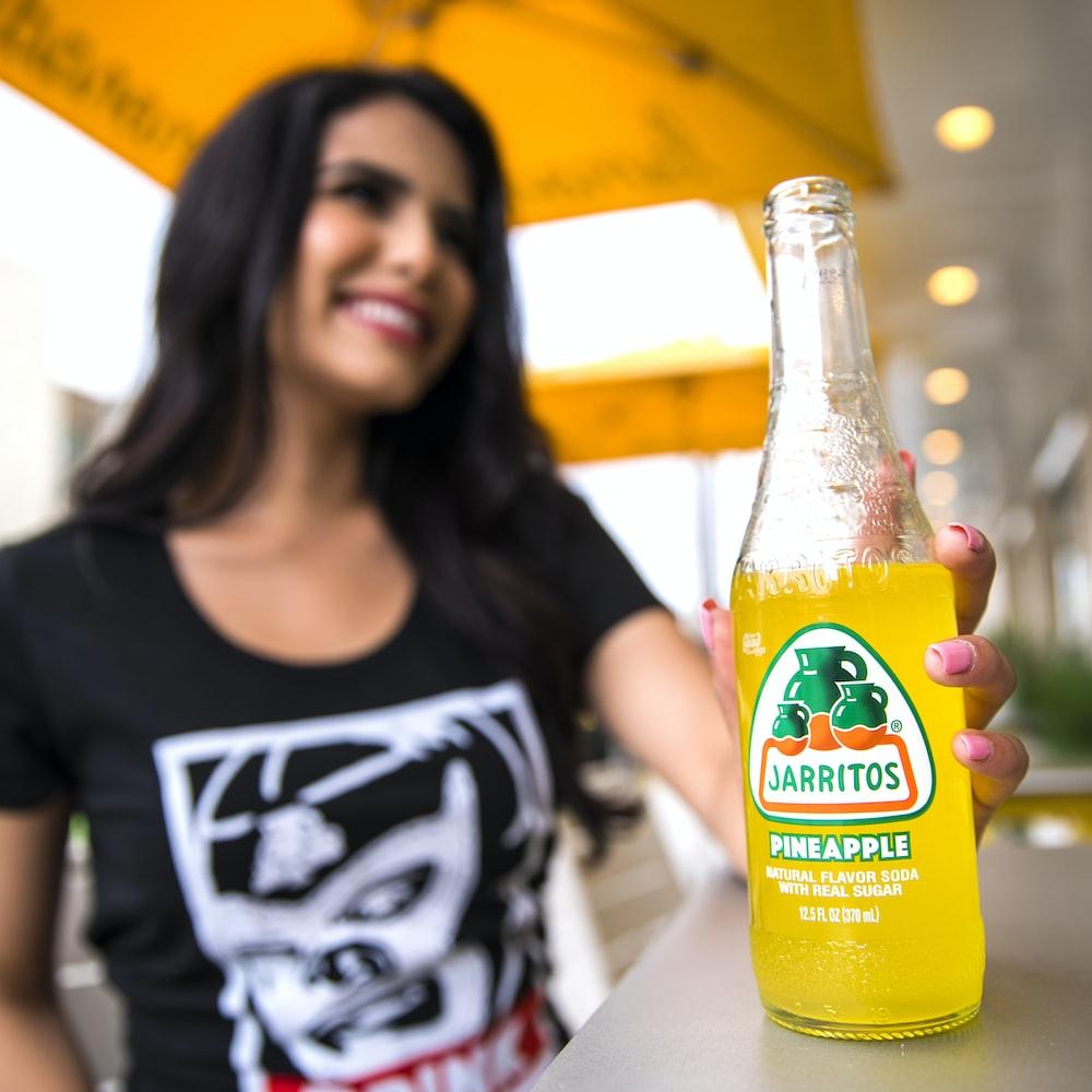 woman in black tank top holding orange juice bottle