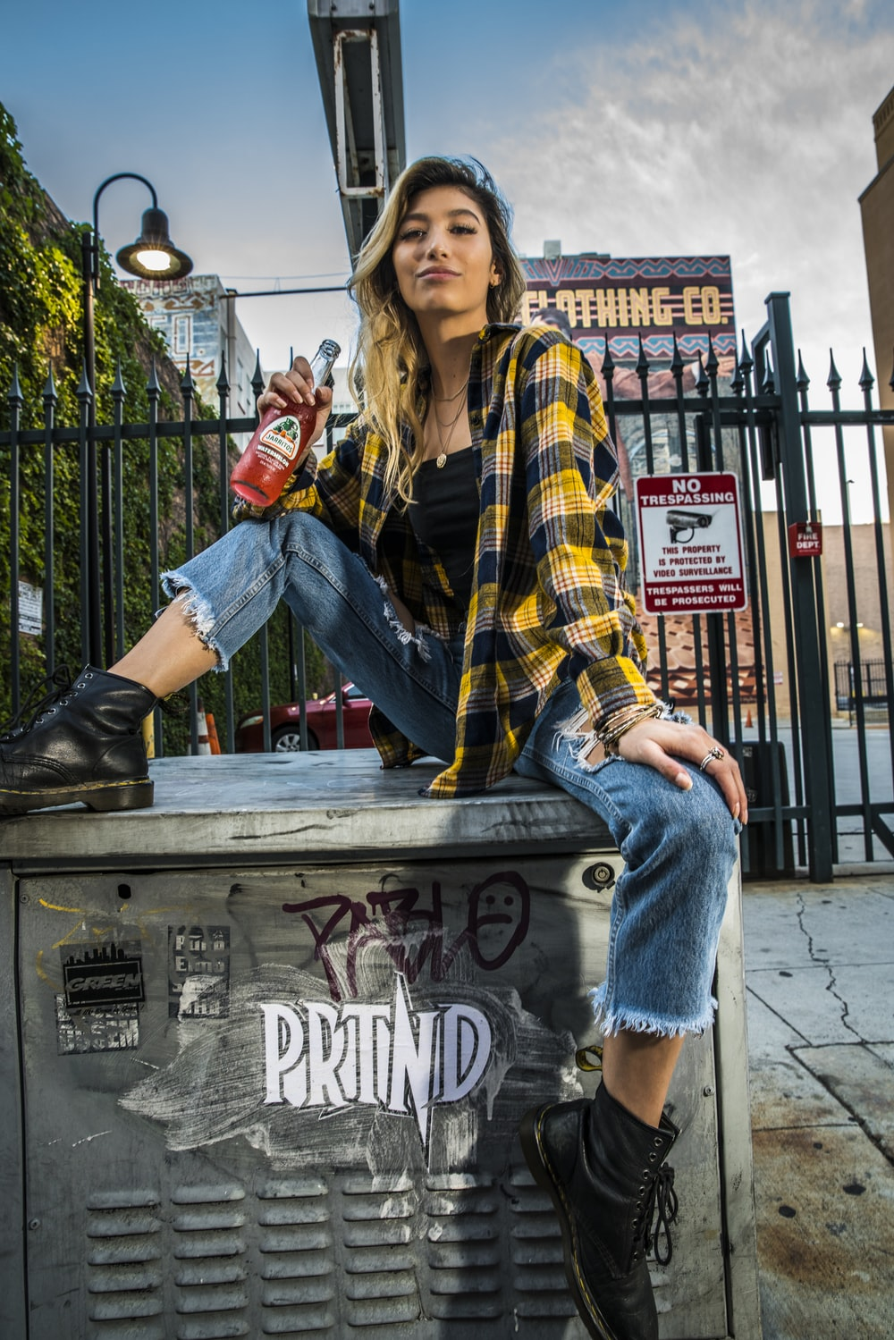 woman in yellow black and white plaid scarf and blue denim jeans sitting on brown wooden